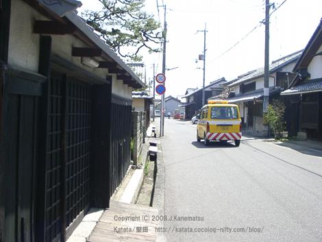 本堅田1丁目の古い町並み。大津市の黄色いパトロールカーが走ってゆく。