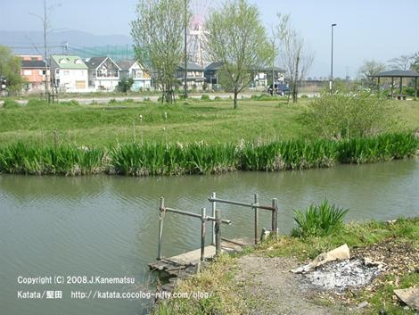 手前に小川と小さな船着場、真ん中は新緑の公園とバス停、奥に御菓子の家のような新しい家が数軒と遊園地の観覧車も見えている。