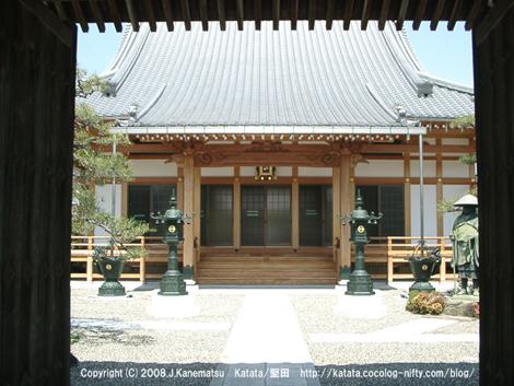 泉福寺の門からお寺をのぞいている。きれいなお寺と蓮如の像が見えている。