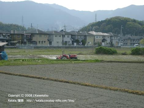 赤いトラクターと住宅街