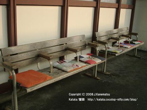 堅田駅のベンチの上に座布団が置かれている。座布団は手作りで、みんな模様が違う、とてもきれいなもの。夕日が差し込んでいる。