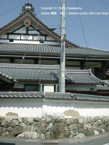 本福寺を近くから見ている。路地の塀は、時代劇に出てくるお城のように古くて立派なもの