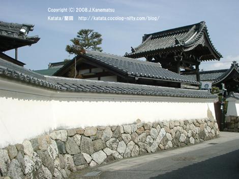 お城を思わせる古くて立派な壁が続く。向こうに本福寺の門が見えている。