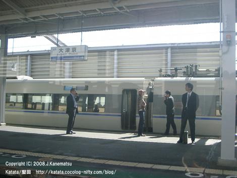 大津京駅のホーム。腕組みをした若い男性が一人、携帯電話をかけるサラリーマンが二人、アタッシュケースを足元においてホームに立っている男性が一人見える。