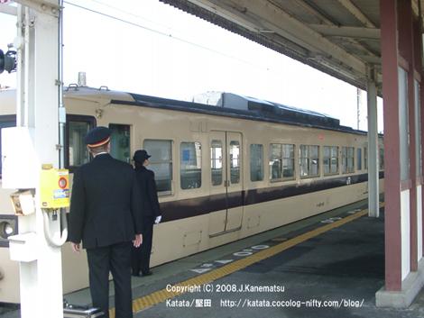 堅田駅のホームをまもなく発車しようとしている電車。若い女性の車掌と中年男性の駅員が電車を見守る。