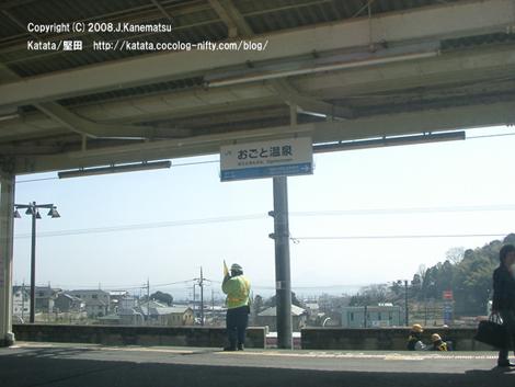 駅のホームで無線機を持って連絡を取る作業員の男性。線路には二人作業員の男性が見える。