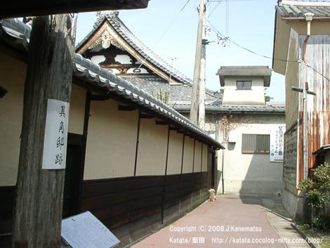 路地の奥、左上の空に光徳寺の立派な瓦屋根が見え、左手に其角亭跡の黄色っぽい塀が続く