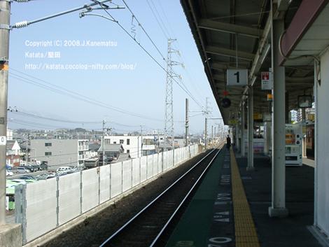 堅田駅1番線ホーム。左手に町、春の空、ホームの奥に人がひとり見える。
