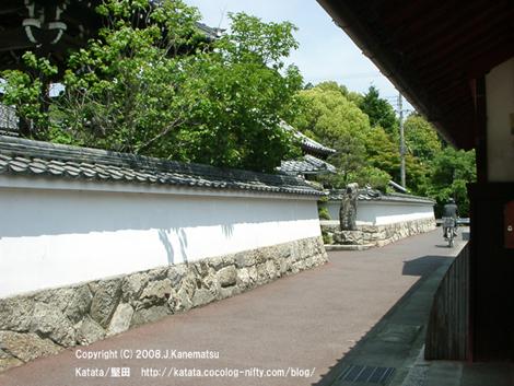 路地の左側に白壁の塀が続く。その途中に光徳寺の門が見えている。自転車の男性が通り過ぎていった。