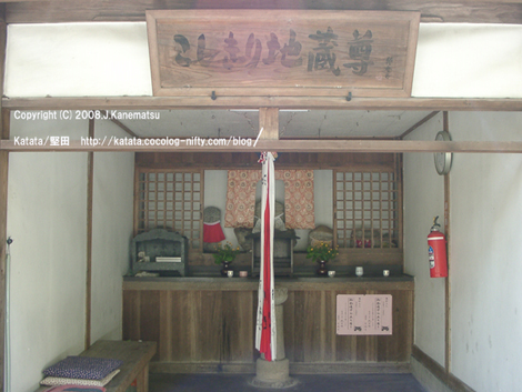 地蔵堂の奥に地蔵が3体並ぶ。左側には座布団を置いた木のベンチ。