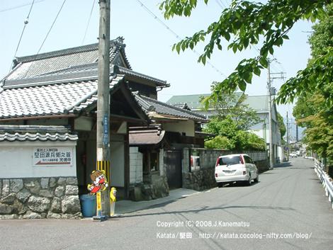 車道、停めてある白い車、地蔵堂、寺の瓦屋根、保育園の建物、右手には木の緑
