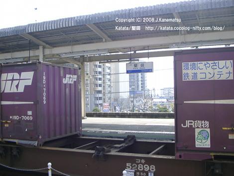 堅田駅のホームにJR貨物が止まっている。コンテナを積んでいない写真中央部分から、駅名の看板と駅のロータリーが見える。