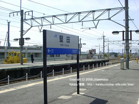 4月の青い空と黄色い除雪車と堅田駅のホームに立つ中年男性