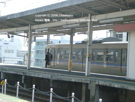 堅田駅の反対側のホームから113系が発車しようとしている。車掌が電車に乗り込むところ。