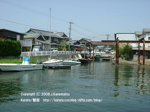 琵琶湖に近い水路に浮かぶ数隻の小船。奥には民家と、造船所の錆びた鉄製の柱が見える。