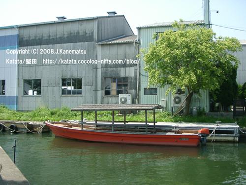 琵琶湖近くの水路に浮かぶ赤い船。後ろには水色と灰色の造船所の建物、緑の木。