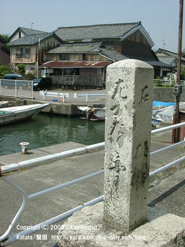 道標、係留されている小船、趣のある水辺の民家