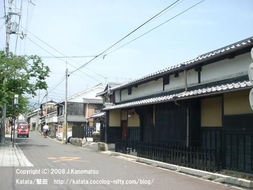 桜の並木道、景観に配慮された町並み、日傘の女性、郵便局の赤い車