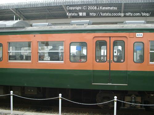 堅田駅のホームにしばらく停まっている電車。ガラス越しに、女性の横顔、男性の後姿。