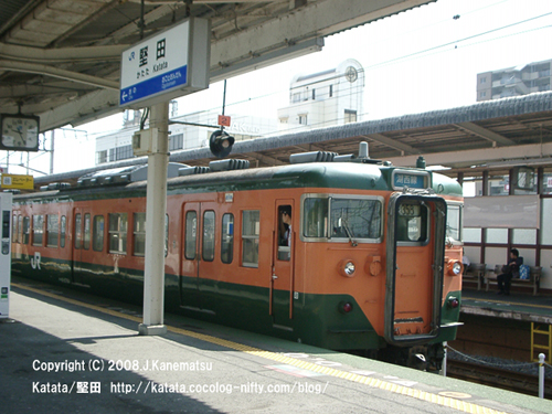 オレンジと緑の113系電車がホームから出て行くところ
