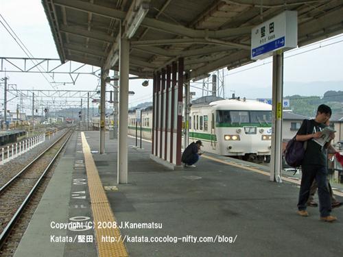 1番線ホームに入ってくる117系電車。携帯電話をいじりながらしゃがみこむ男性。