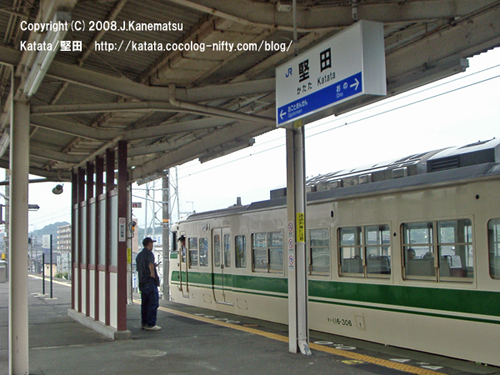 117系電車がホームに停車する。ホームに立つ男性と、後ろの窓から顔を出す車掌。