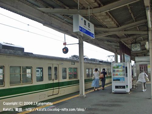 扉が閉まった直後の117系電車とホームを歩いてゆく夏服の3人の女性の後姿