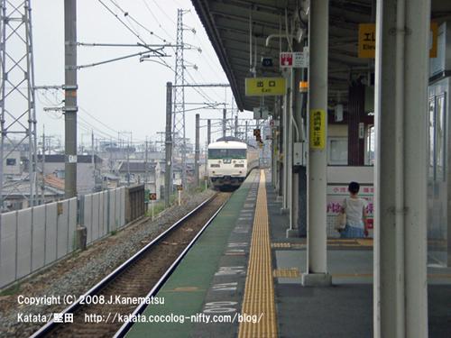 駅から遠ざかる117系電車と駅の階段を下りてゆく女性の後姿