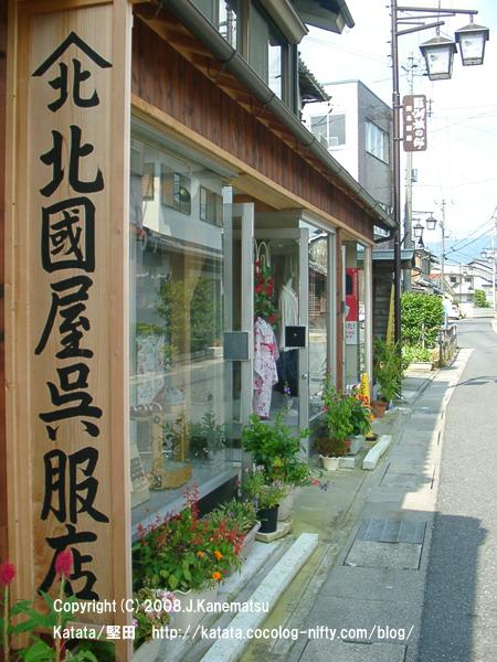 老舗の呉服店。店先に女児用の浴衣が飾ってある。店先には赤、オレンジ、ピンクの花。