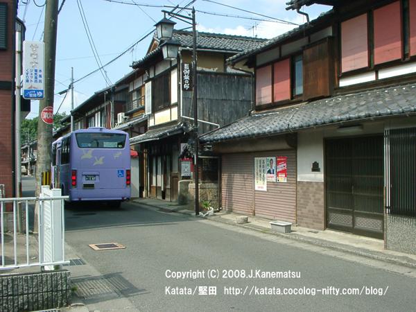 2階の窓の赤が印象的な古い町並み、ラベンダー色のバス、地蔵堂、堅田湯のサウナの看板