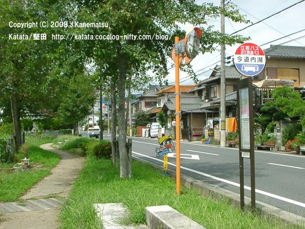 緑の並木道とバス停、公道を通り過ぎていったトラクターと住宅街