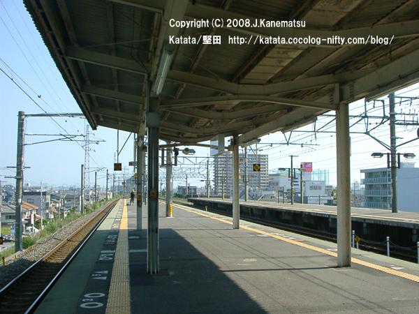 堅田駅の一番線ホームの先頭部分を、同じホームの真ん中から見ている。電車を待つ若い男性が一人、見える。