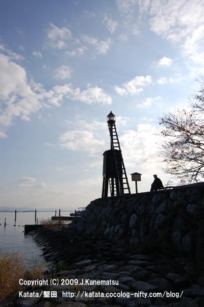 灯台の横のベンチに腰掛けて琵琶湖を眺める男性