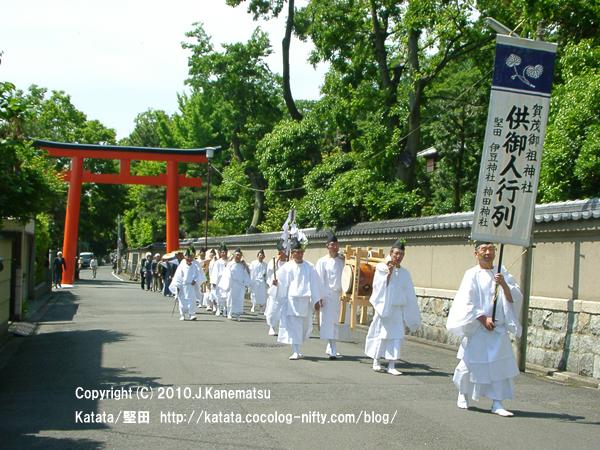 朱色の鳥居をくぐり、新緑の中を下鴨神社へ向かって進む一行