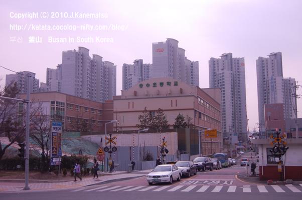 電車の踏切、車、人、高層ビル群、釜山の街
