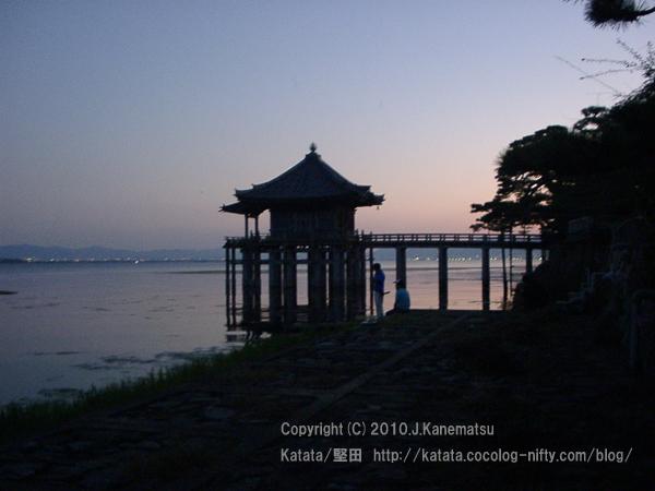 秋の夕暮れに、琵琶湖岸、浮御堂前で話をするふたり