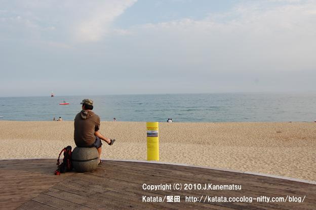 韓国・釜山の浜辺で海を見ていた青年