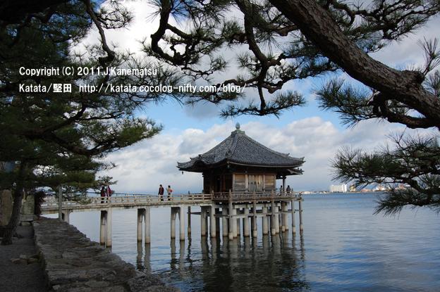 琵琶湖の上に架かる石橋を渡って、浮御堂に参拝する人