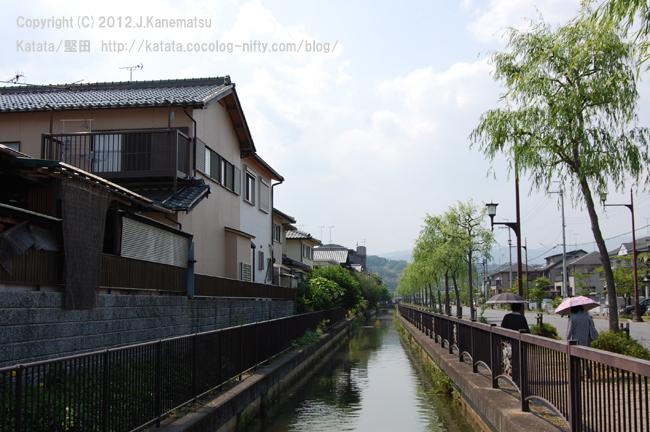堅田内湖から引かれた水路が、初夏の町を巡る。街路樹と、家と、日傘の女性と。